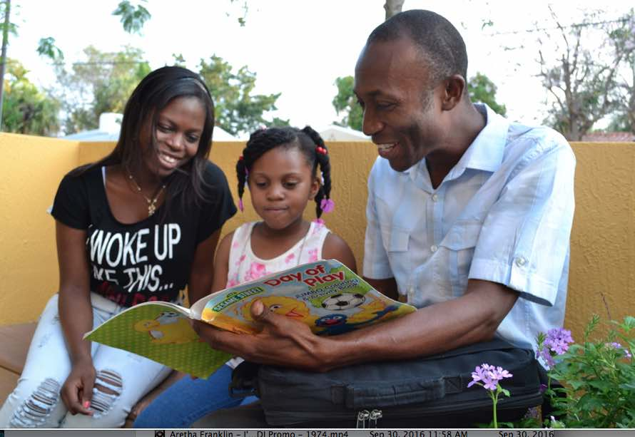 Henri Francois reads to his daughters